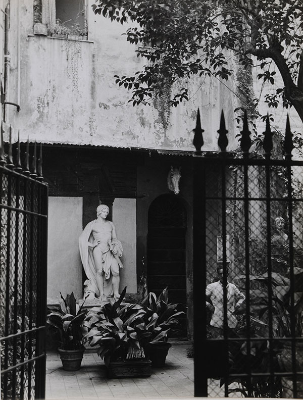 """Statue behind gate with onlooker. (10.5"""" x 14""""). Islay LYONS."""