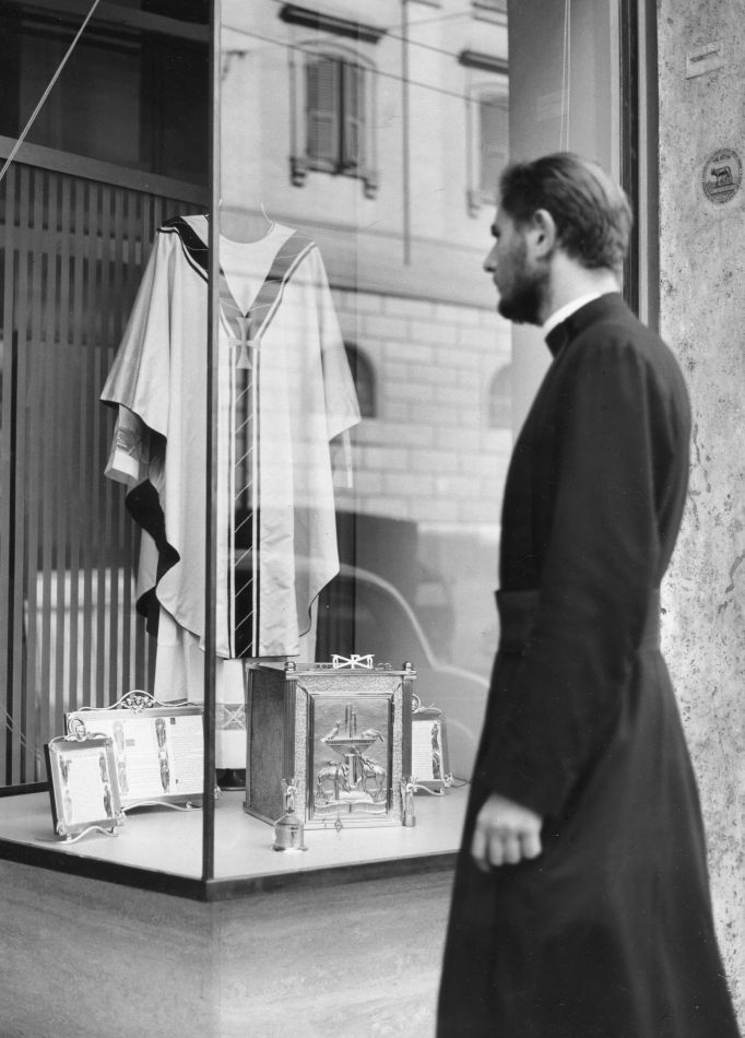 """Priest window shopping, Rome. (9"""" x 12""""). Photographer's stamp on verso with penned inscription. Islay LYONS."""